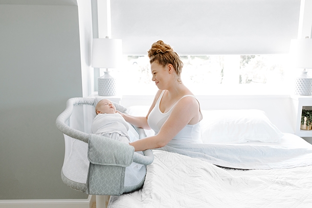 Mum pulling baby from HALO BassiNest Essentia from bed