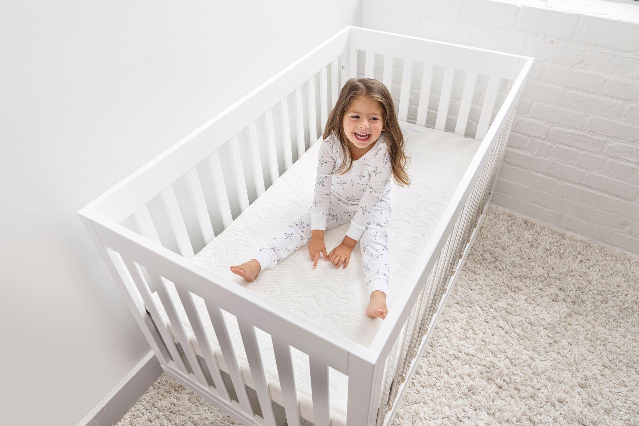 toddler girl sitting in crib on halo dreamweave breathable crib mattress