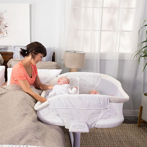 Mum tends to baby in HALO BassiNest Twin from bed