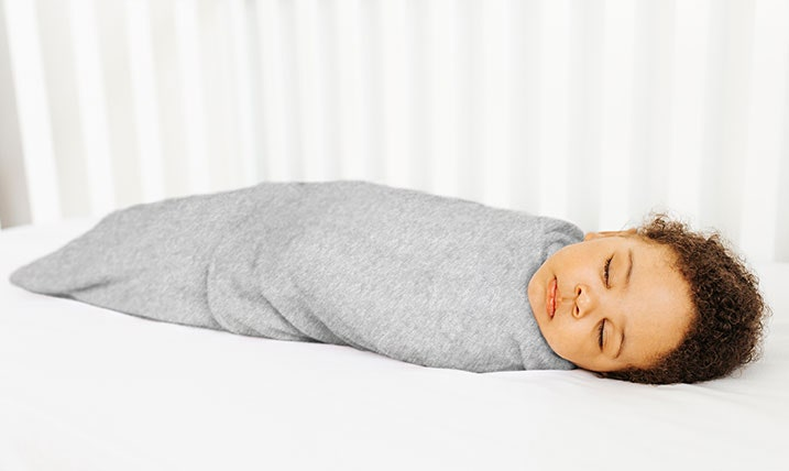 Baby sleeping in the cot with the HALO SleepSack swaddle 1.5 TOG Heather Grey
