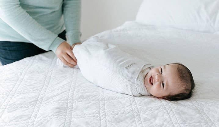 Mum safely swaddles her baby with HALO SleepSack Swaddle