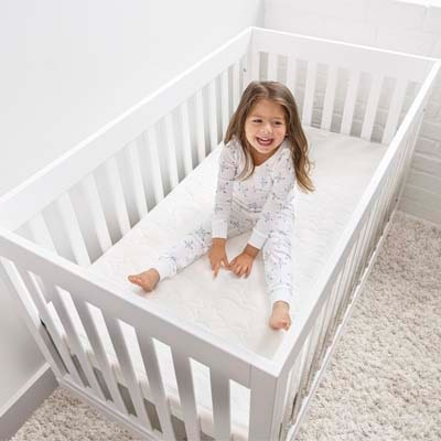 toddler girl in clear crib with breathable crib mattress