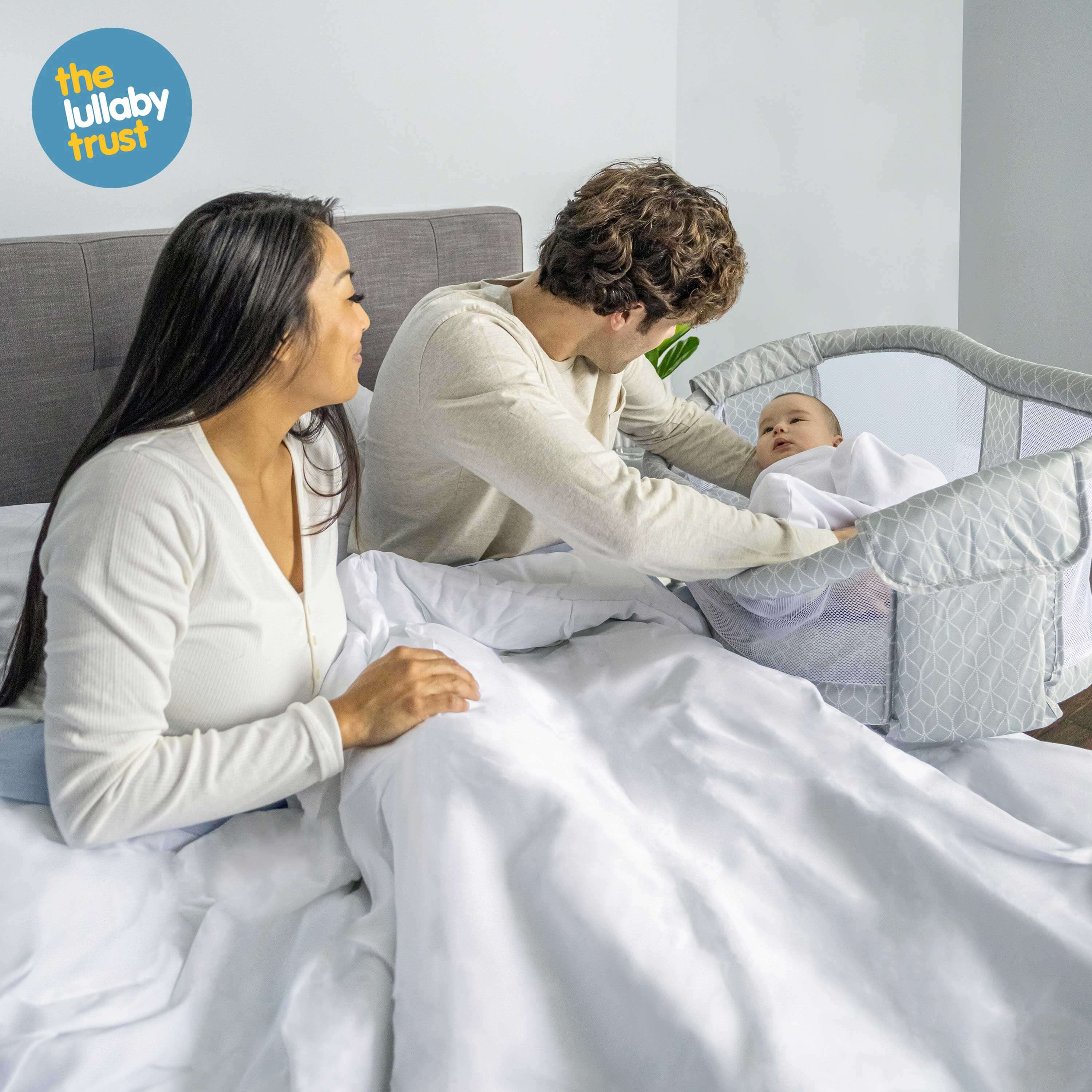 Mum and dad in bed next to baby sleeping in the HALO BassiNest Essentia