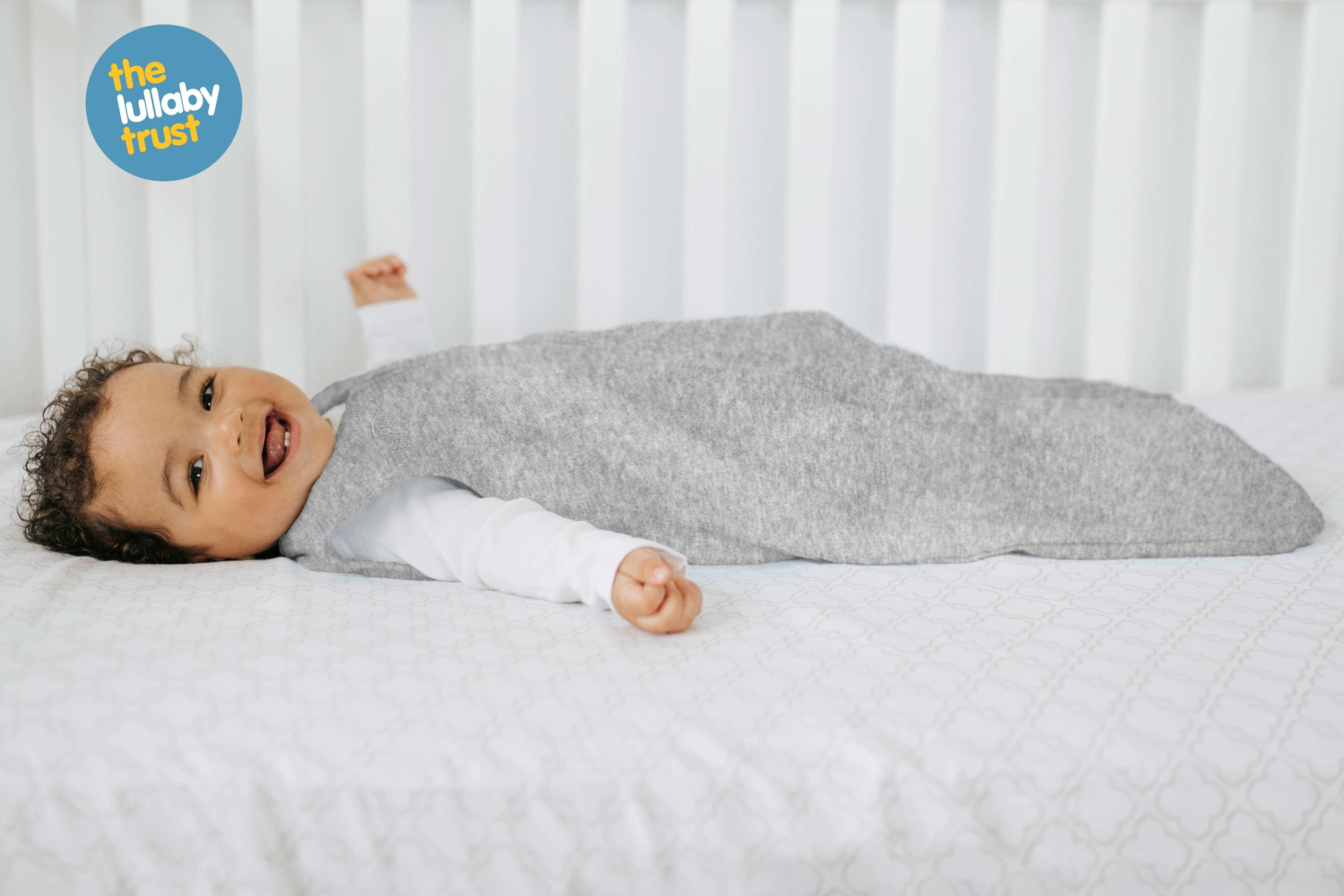 Baby smiling while wearing HALO SleepSack sleeping bag 0.5 TOG Heather Grey