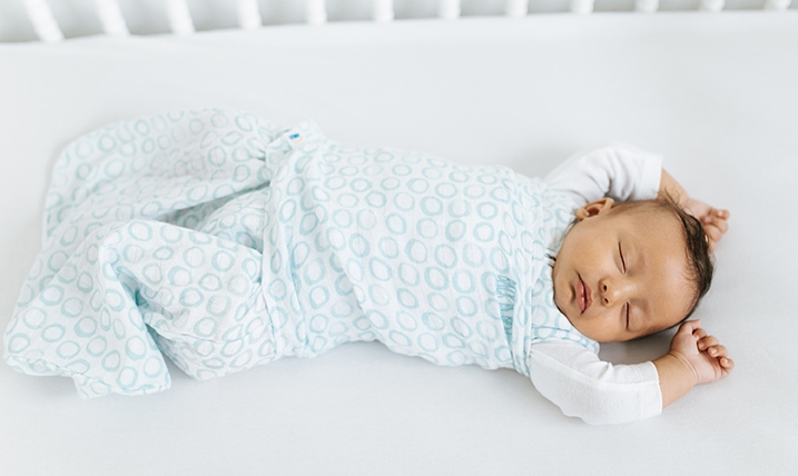 Baby sleeping with both arms out of the HALO SleepSack Swaddle